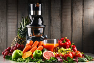 Large juicer surrounded by fruit and veggies